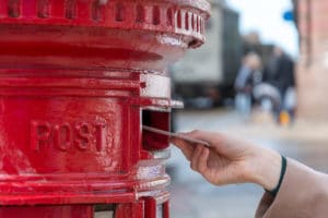 Throwing a letter in a red British post box